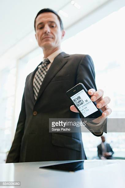 Business man scanning digital boarding pass at airport