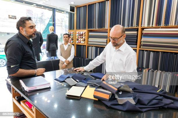 business man selecting fabric for a custom tailored suit - custom tailored suit stock pictures, royalty-free photos & images