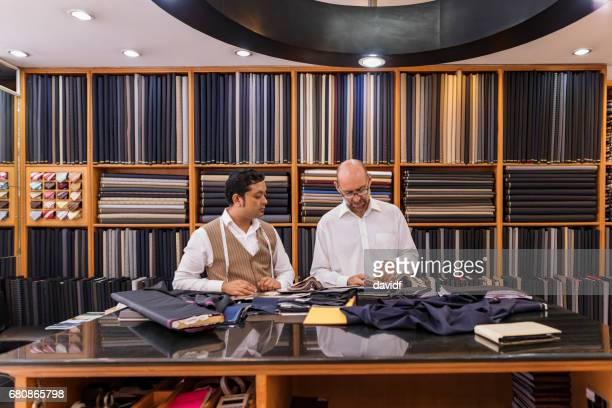 business man selecting fabric for a custom tailored suit - all shirts stock pictures, royalty-free photos & images
