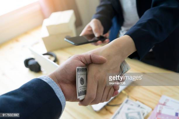 business man shake hand after agree deal with us dollar money in his hand over workspace - corruption stock pictures, royalty-free photos & images