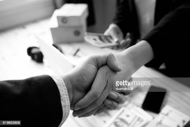 Business man shake hand after agree deal with Us dollar money in his hand over workspace