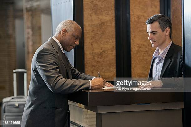 Business man signing into hotel