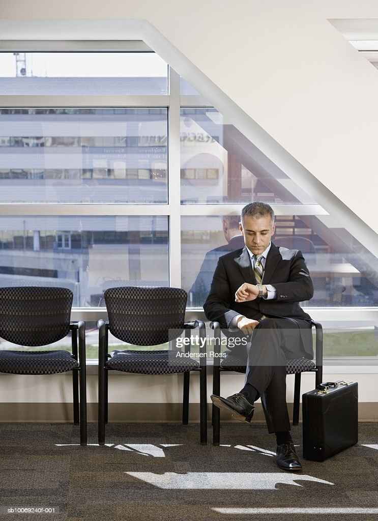 Business man sitting and checking time : Stockfoto