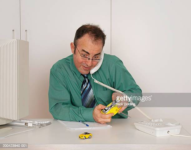 business man sitting at desk playing with remote control car - remote control car games stock pictures, royalty-free photos & images