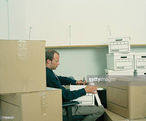 Business man sitting between boxes in office