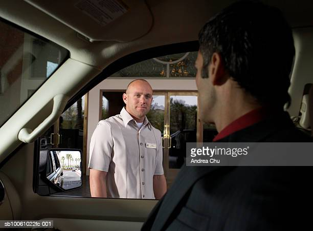 Business man sitting in car looking at bellhop standing on hotel driveway