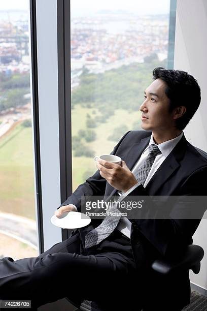 Business man sitting in chair, drinking cup of coffee in front of window