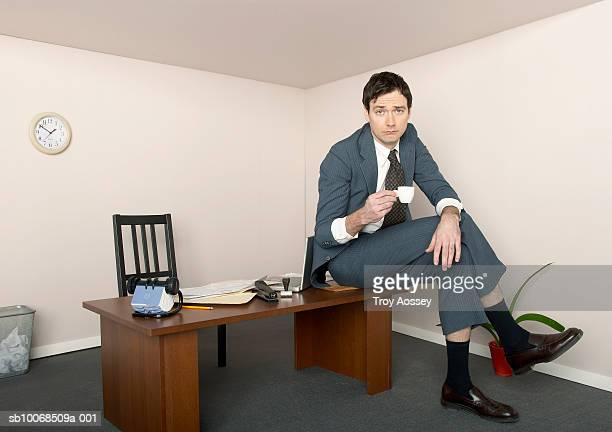 Business man sitting on desk holding coffee cup in miniature office, portrait