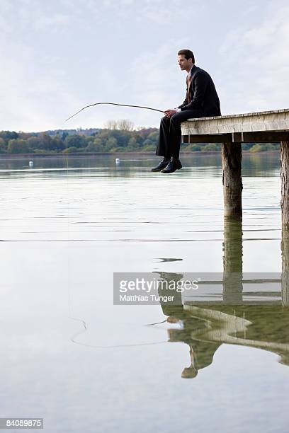 Business man sitting on edge of pier, fishing