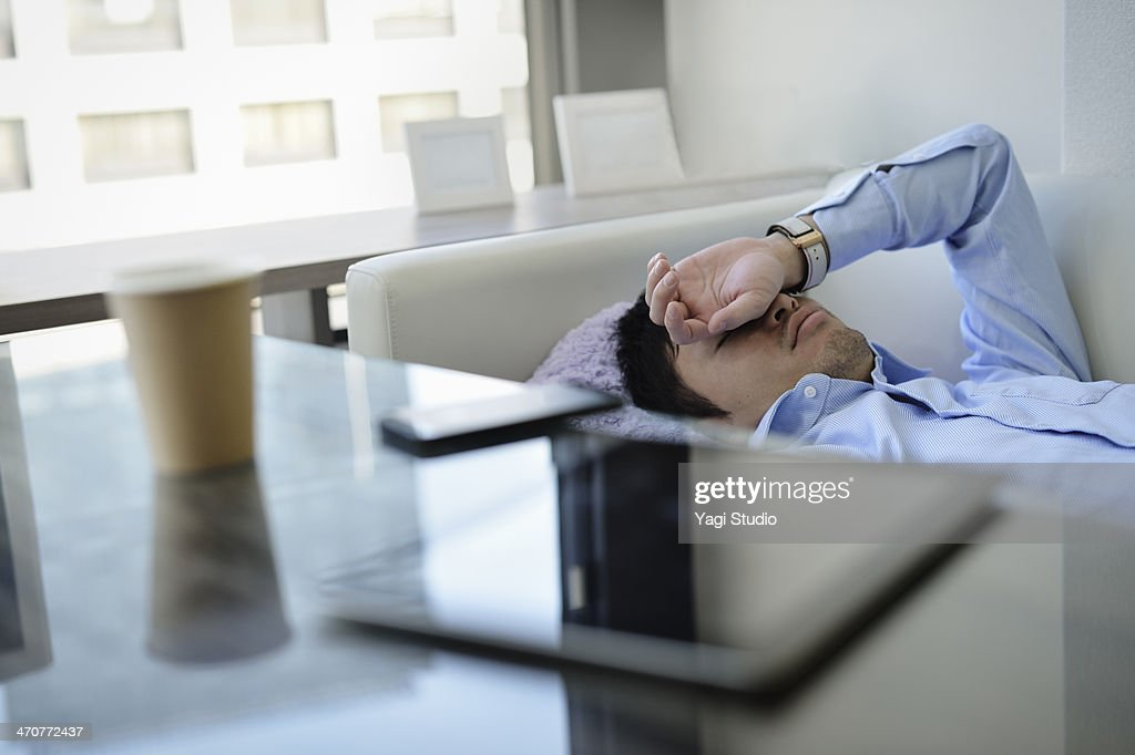Business man sleeping on the sofa in office : Stock Photo
