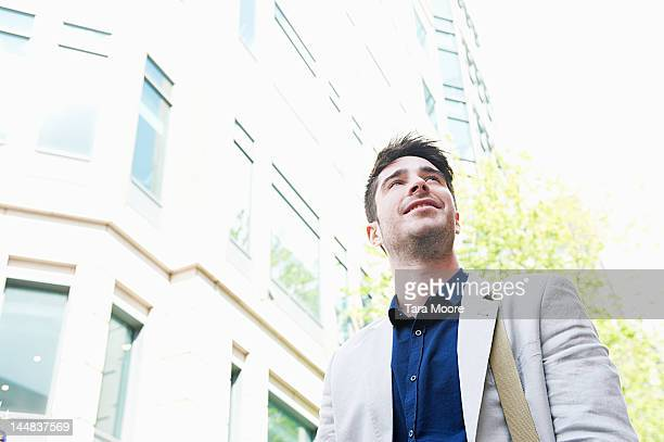 business man smiling and looking up in the city - newtechnology stock pictures, royalty-free photos & images