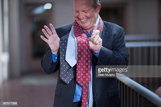 business man smiling, wearing many ties - multi colored suit stock photos and pictures