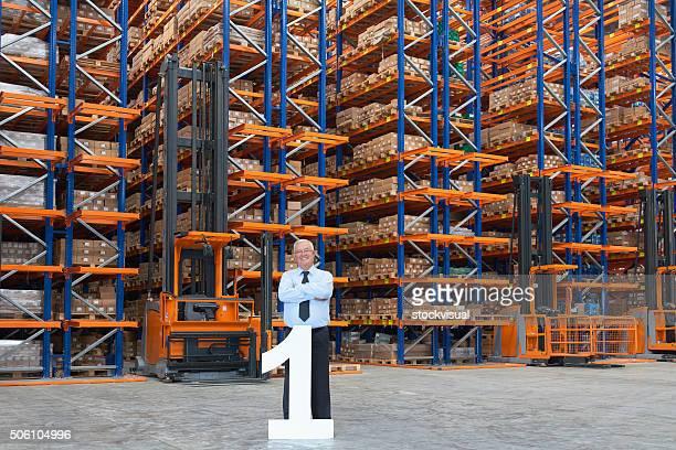 ビジネスの男性の後ろに大きな番号 1 の倉庫