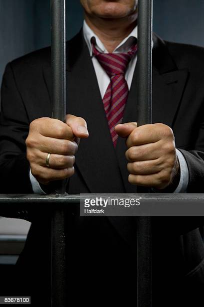 A business man standing behind prison cell bars