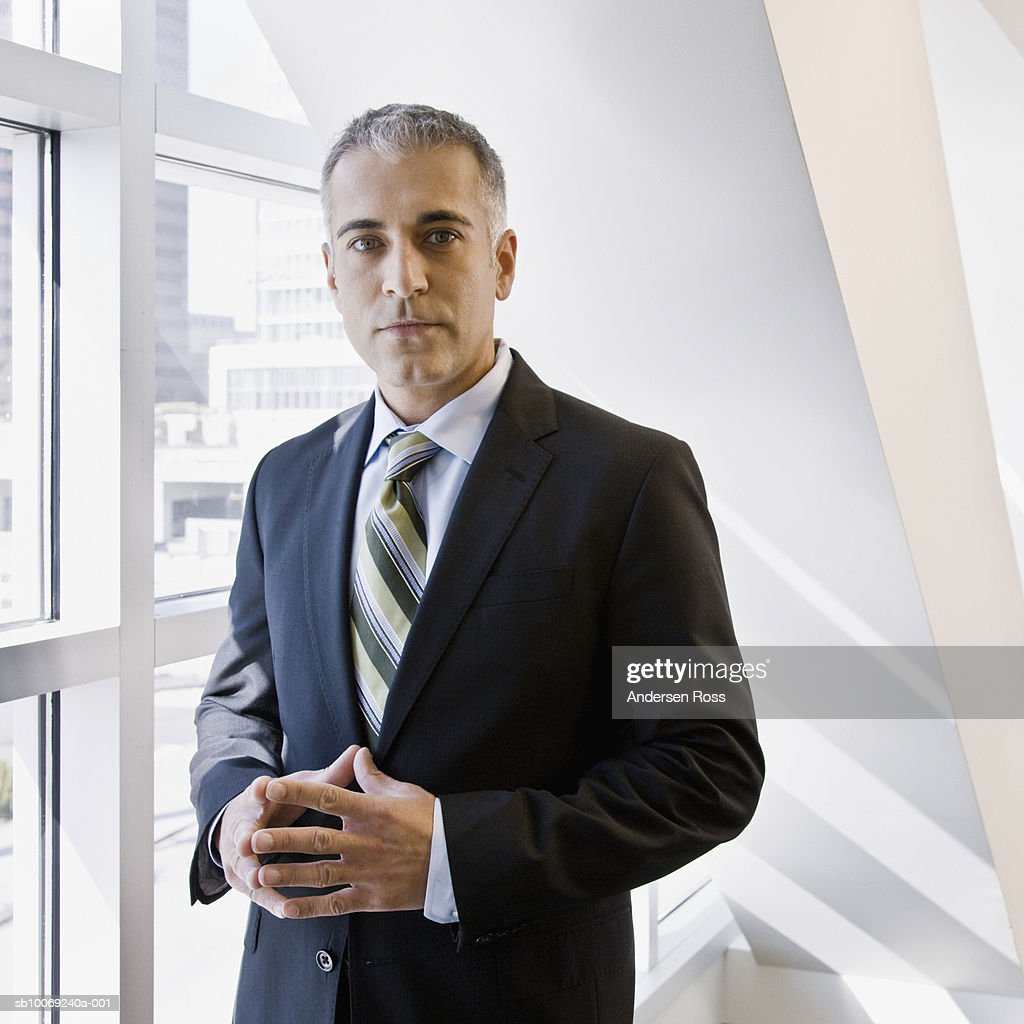 Business man standing by window, portrait : Stockfoto