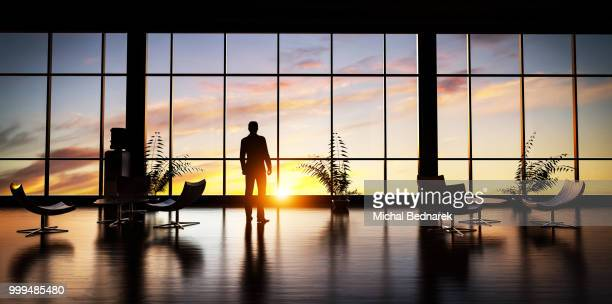 Business man standing in the office looking out of the window at sunset sky.