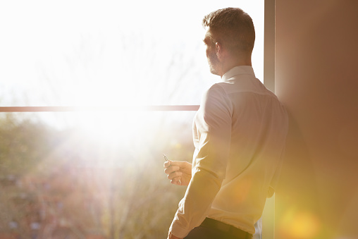 business man standing my window with sunlight - gettyimageskorea