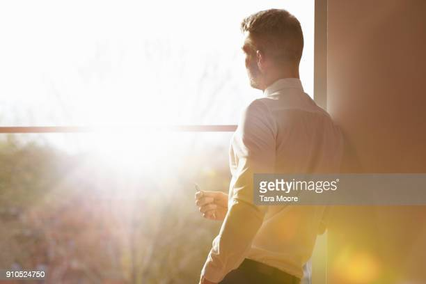 business man standing my window with sunlight - sonnenlicht stock-fotos und bilder