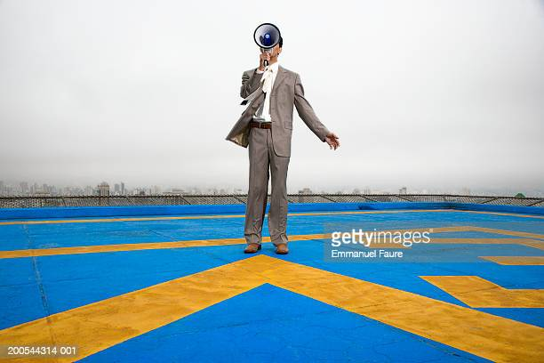 Business man standing on heliport with megaphone