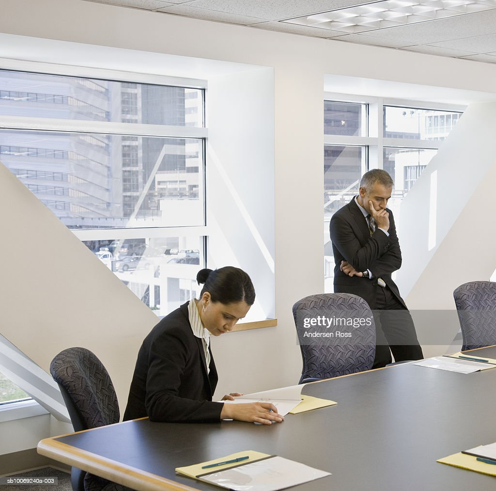Business man standing with hand on chin while woman working in conference room : Stockfoto