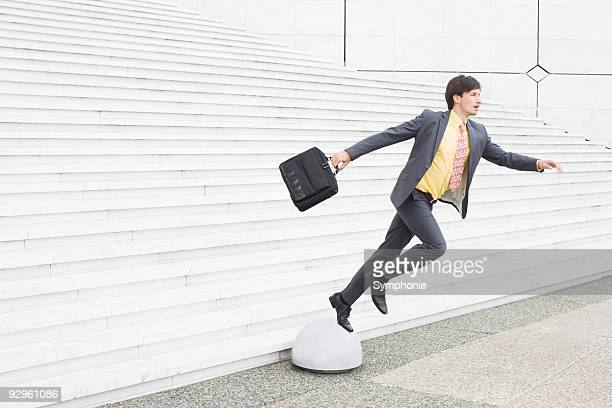 Business man stepping off of low pedestal
