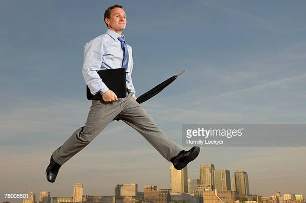 business man striding across city skyline - striding stock pictures, royalty-free photos & images