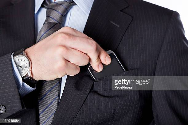 Business man taking the smartphone out of his pocket