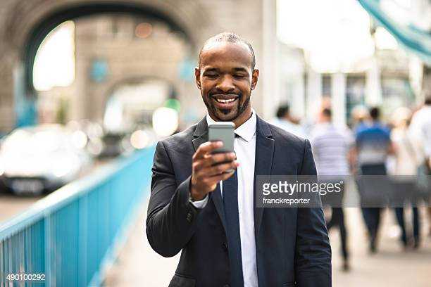 Business Mann SMS auf der tower bridge in London
