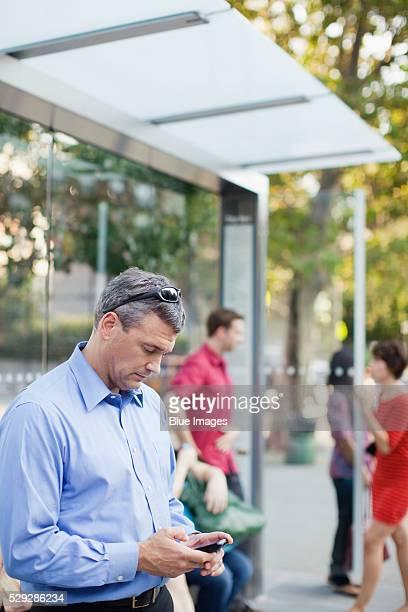 Business man texting at bus stop