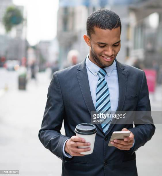 Business man texting on his cell phone and having coffee to go