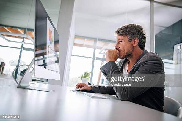 Geschäft Mann Gedanken über Statistiken, Grafiken auf dem Bildschirm.
