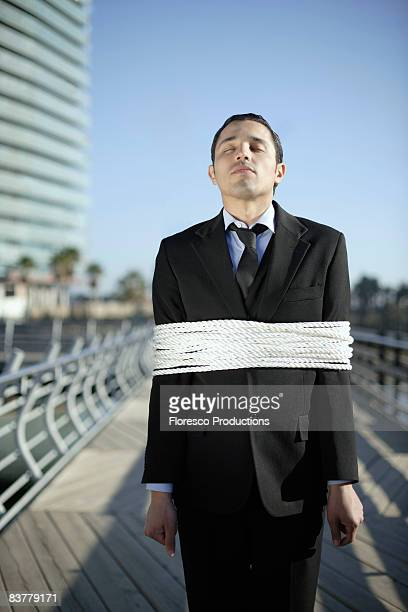 Business man tied up with ropes outdoors