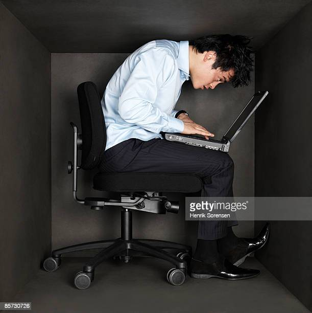 Business man trapped inside a small black room