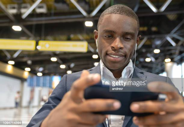 Business man traveling and using his cell phone with headphones at the airport