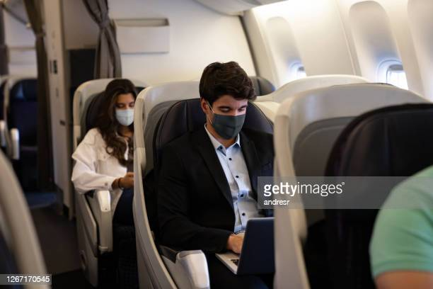 business man traveling and wearing a facemask on the plane - passenger stock pictures, royalty-free photos & images