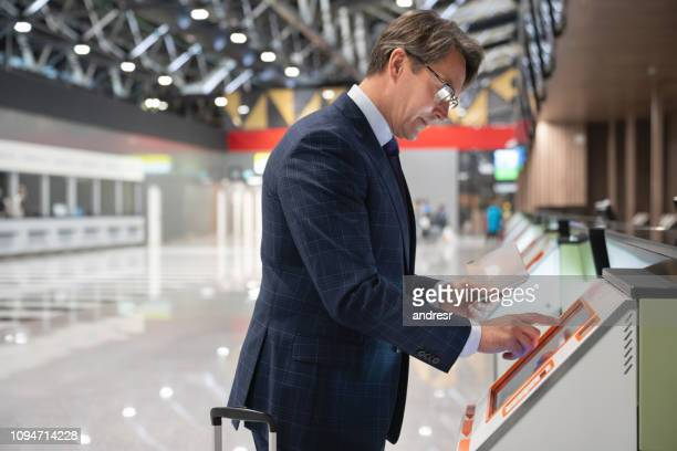 Business man traveling by plane and doing the self check-in at the airport