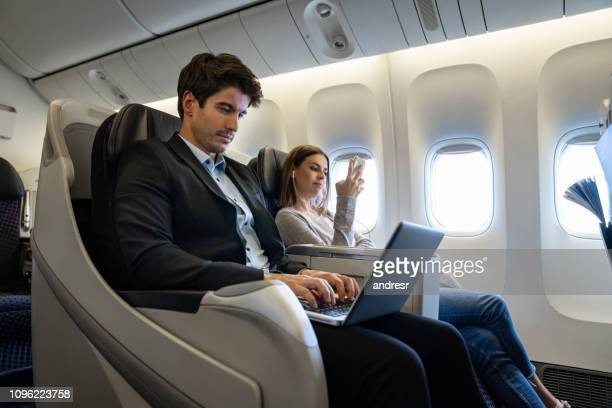 business man traveling by plane and working on his laptop - business travel stock pictures, royalty-free photos & images
