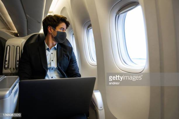 business man traveling by plane wearing a facemask and using his laptop - air vehicle stock pictures, royalty-free photos & images