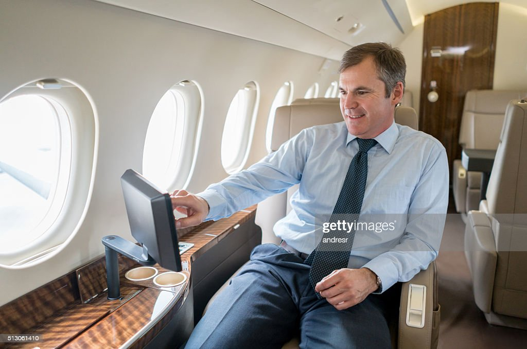 Business man traveling in a private jet : Stock Photo
