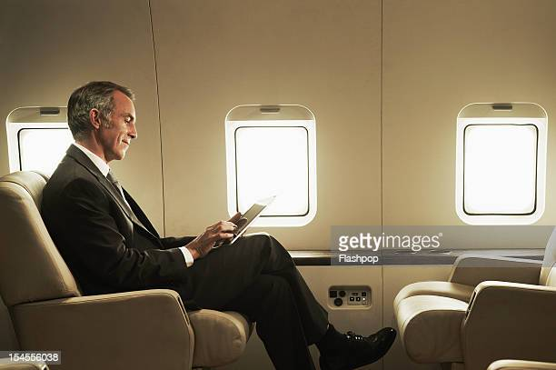 business man travelling aboard a private jet - premium access stock pictures, royalty-free photos & images