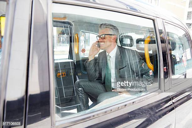 Business man using a smart phone in a taxi
