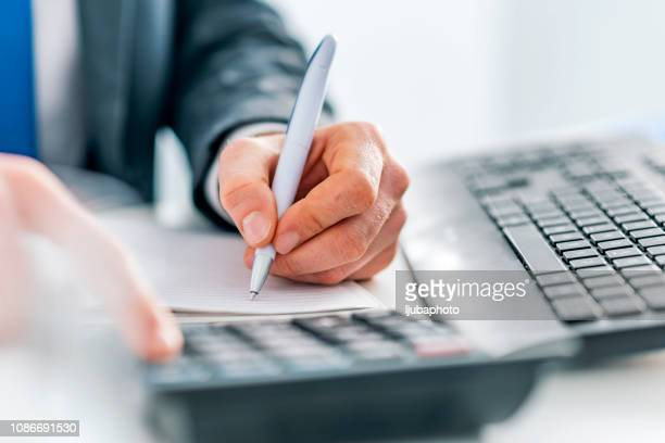 business man using calculator - finanza foto e immagini stock