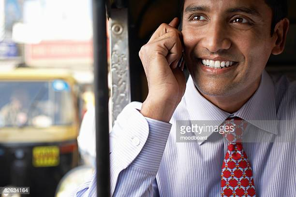 Business man using cell phone, smiling