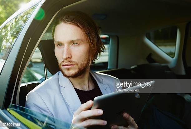 Business man using digital tablet in back seat of car