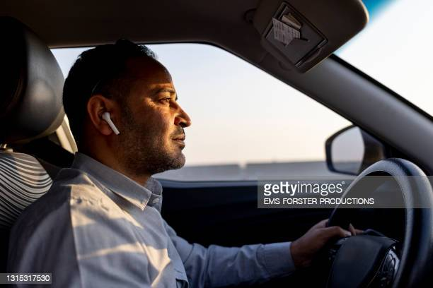 business man using ear pods while driving a car - egypt stock pictures, royalty-free photos & images