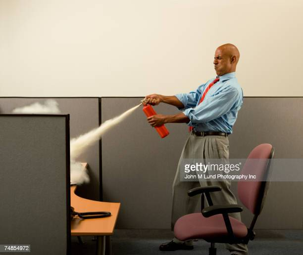 business man using fire extinguisher on computer in cubicle - john lund stock pictures, royalty-free photos & images
