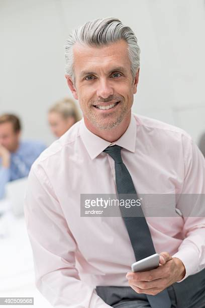 Business man using his cell phone in a meeting