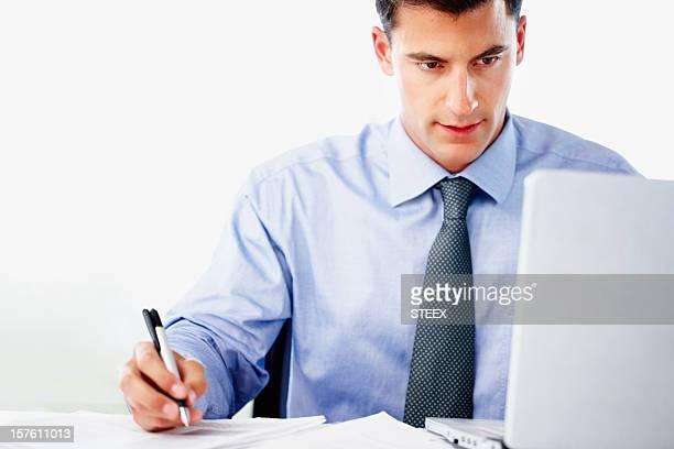 Un hombre de negocios con ordenador portátil y escribir notas