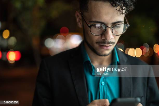 business man using mobile at street - capital cities stock photos and pictures