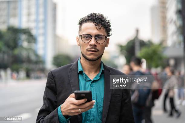 business man using mobile at street - gay man stock pictures, royalty-free photos & images